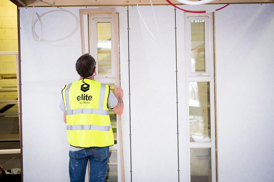 Elite factory worker fitting windows on a modular building