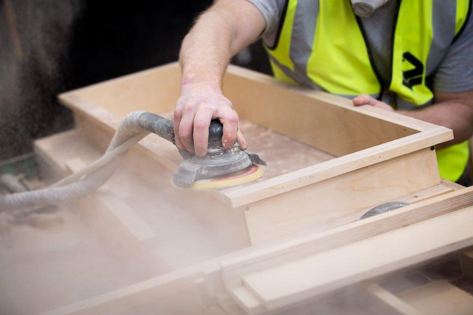 Elite factory worker using a sander